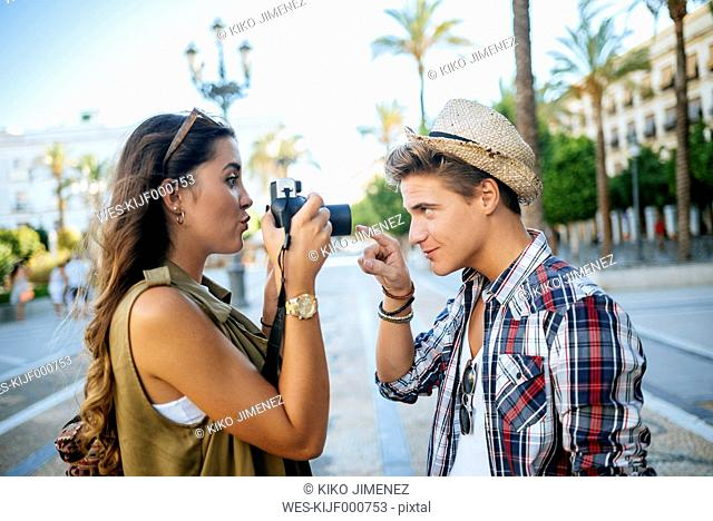 Spain, Jerez de la Frontera, young woman taking picture of her boyfriend