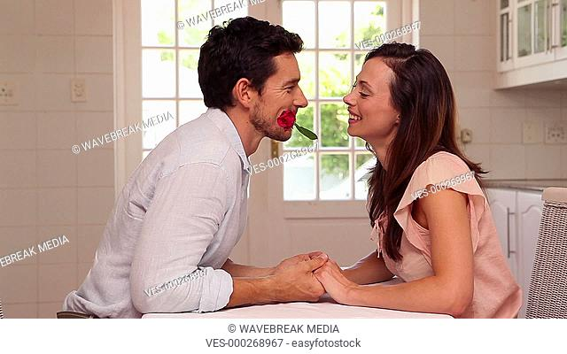 Happy man giving his partner a rose from his mouth