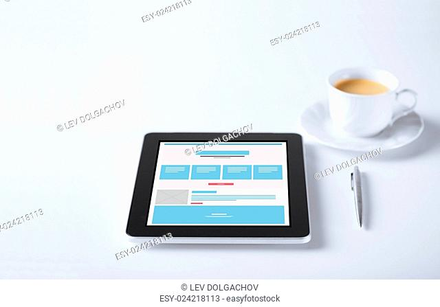 business and technology concept - close up of tablet pc computer with web page design template and cup of coffee