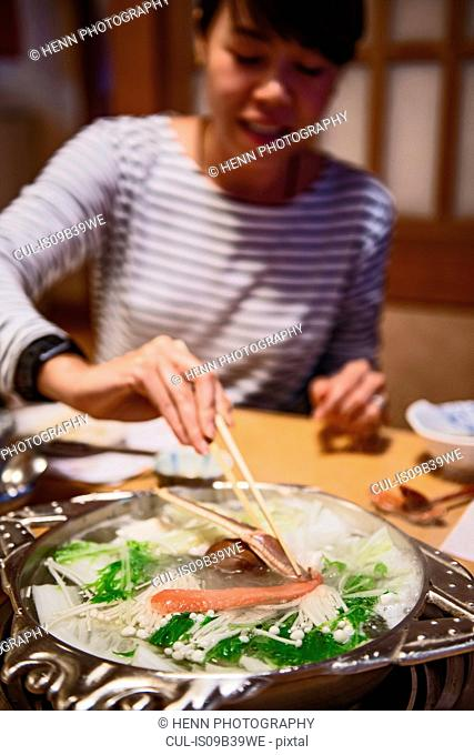 Woman eating crab with chopsticks, Kyoto, Japan