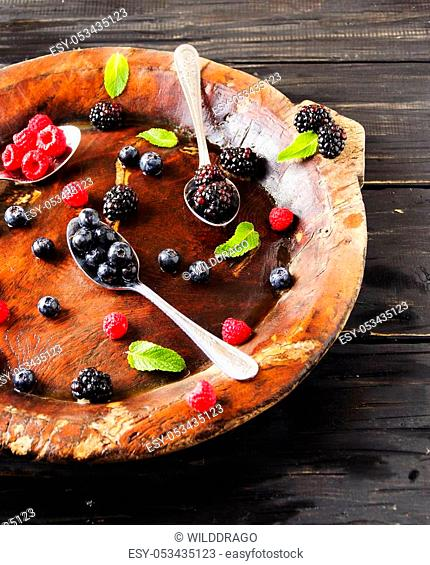 fresh ripe berries raspberries blackberries and blueberries on a brown wooden plate with a spoon on a black wooden table, rustic, selective focus
