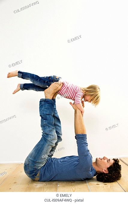 Studio shot of father lifting up daughter whilst lying on back