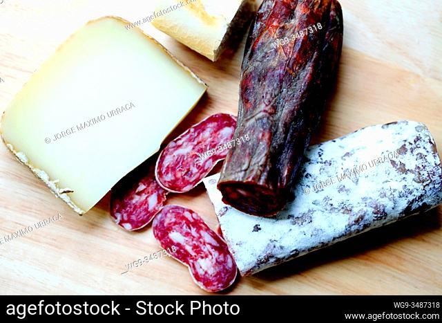 Sausage palette with cheese on a wooden board