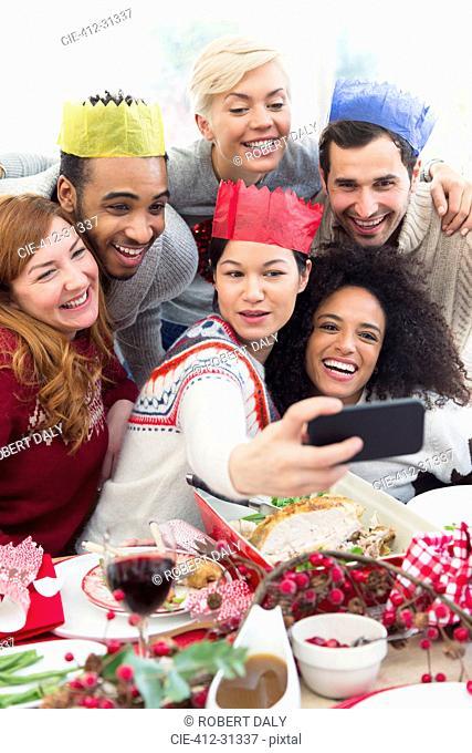 Friends in paper crowns taking selfie at Christmas dinner