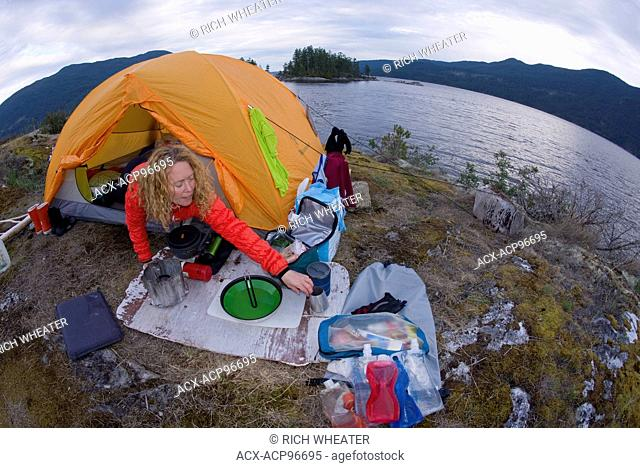 Woman in tent, camping at Kunechin Point, Sechelt Inlet, Gibsons, Sunshine Coast, British Columbia, Canada