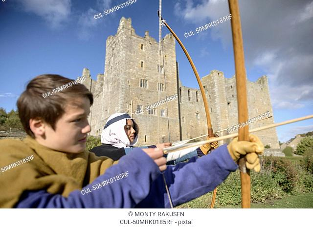 Students in period dress shooting arrows