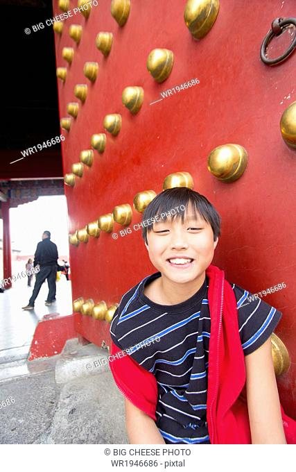 Boy in front of the palace gates in the Forbidden City, Beijing, China