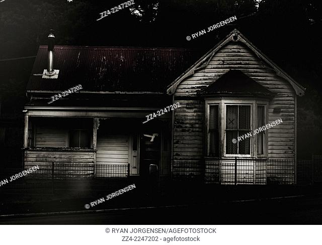 Dark residential exterior fine art on an old abandoned haunted house with a cross on the window and ghostly activity in the cold night air