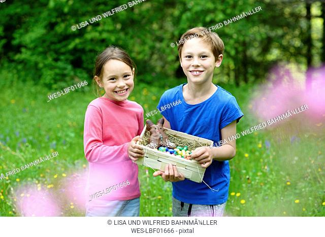 Portrait of little boy and girl holding Easter nest