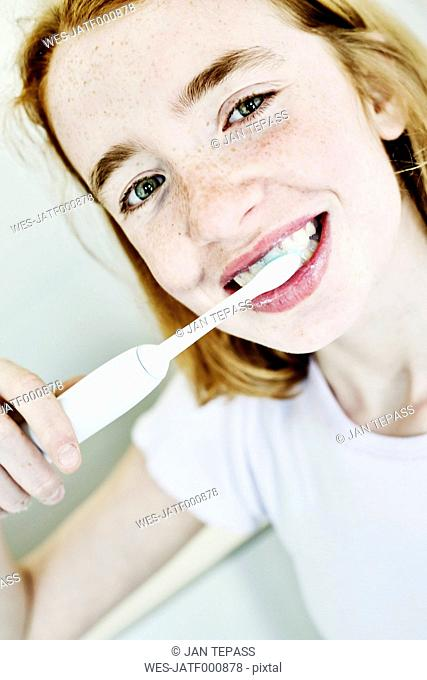 Portrait of smiling girl brushing teeth with electric toothbrush