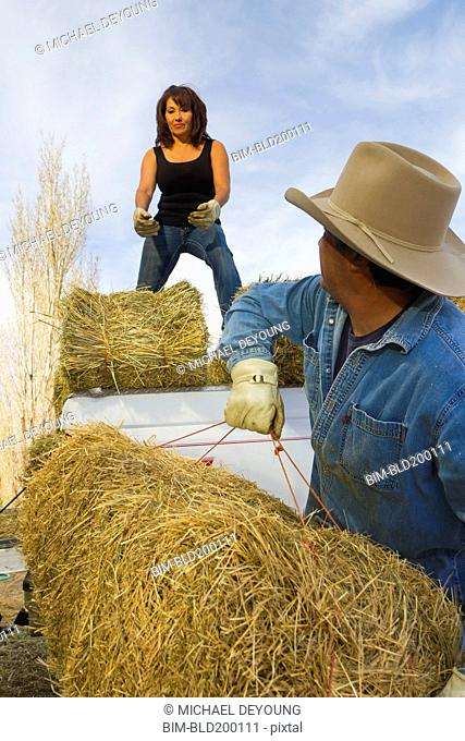 Hispanic couple loading hay