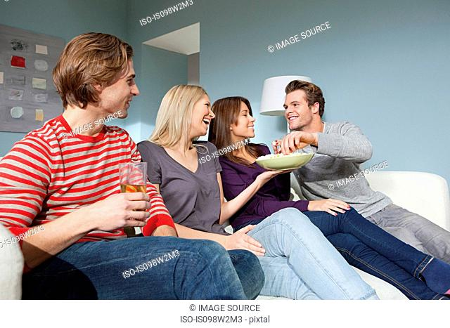 Two young couples watching television