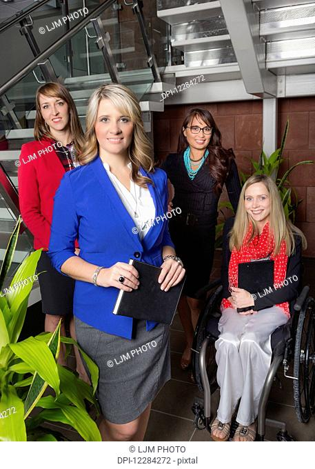 Portrait of a professional business woman with her team in the lobby of an office, one of which is a paraplegic in a wheelchair; St