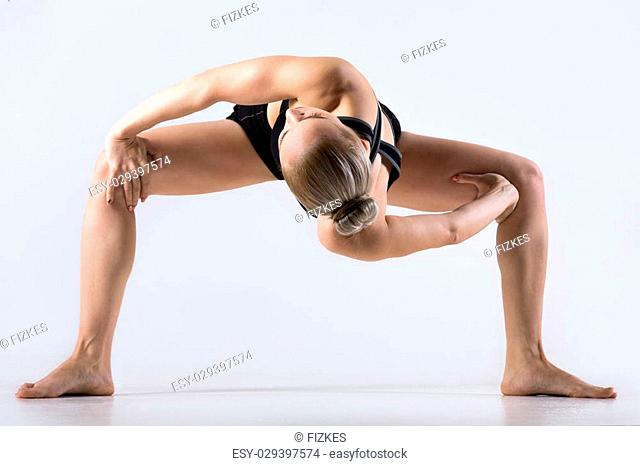 Sporty beautiful young woman practicing yoga, twisting in variation of Goddess, Temple or Sumo Squat Pose, working out wearing black sportswear
