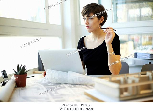 Architect sitting at desk looking through window