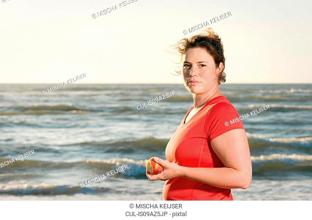 Mature female runner standing on beach at sunset, eating an apple
