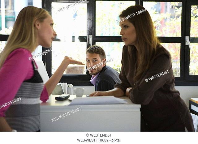 Three Business people in office, women discussing