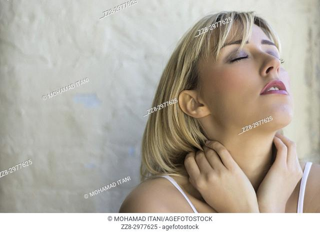 Tired blond woman hands touching neck