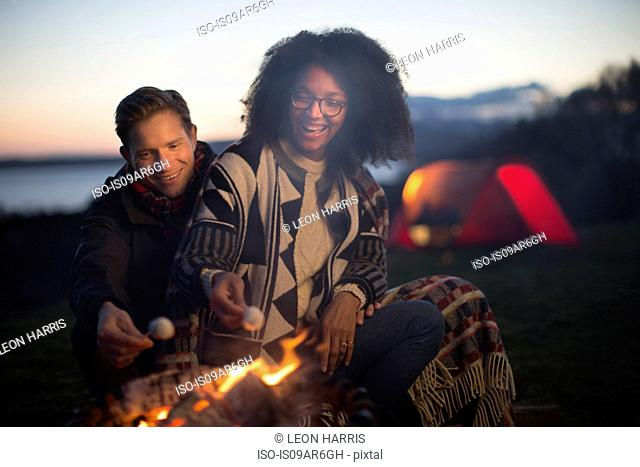 Couple toasting marshmallows at camp, Isle of Skye, Scotland