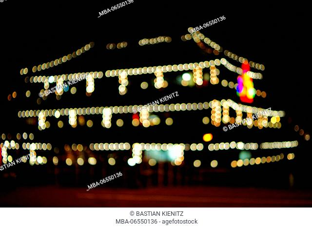 The coloured light circles of the chain of lights of an illuminated restaurant