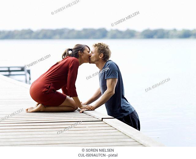 Couple on pier face to face holding hands kissing, Copenhagen, Denmark