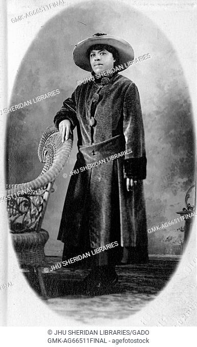 Full length standing portrait of young African American woman next to chair, wearing a long dark coat, a hat, and a neutral expression, 1915