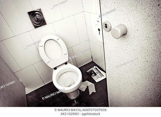 toilet with the door ajar and newspaper on the floor