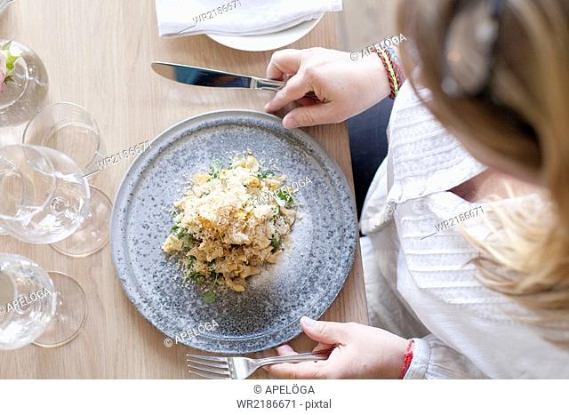 High angle view of woman having smoked Jerusalem artichoke at restaurant table