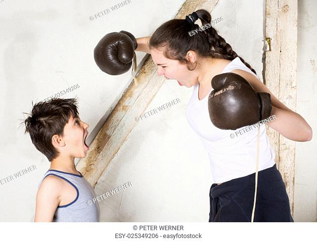 a young boy and a teenage girl are boxing
