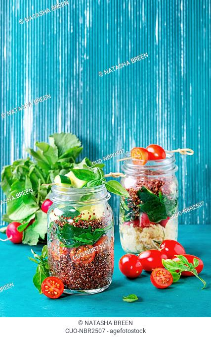 Salads with quinoa, couscous, spinach, radish, tomatoes and zucchini in glass mason jars, standing with fresh vegetables over bright turquoise wooden background