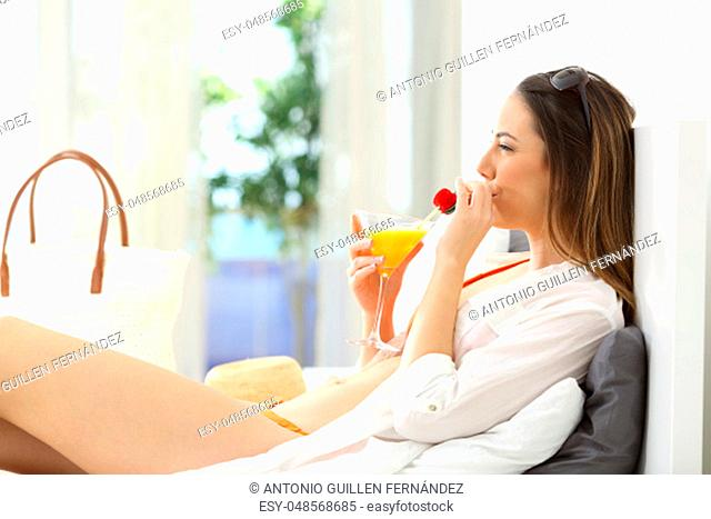 Side view portrait of a woman drinking cocktail on a bed of an hotel room in summer vacations