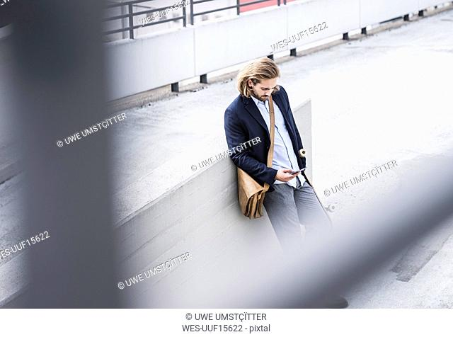 Young businessman with skateboard, leaning on wall, using smartphone