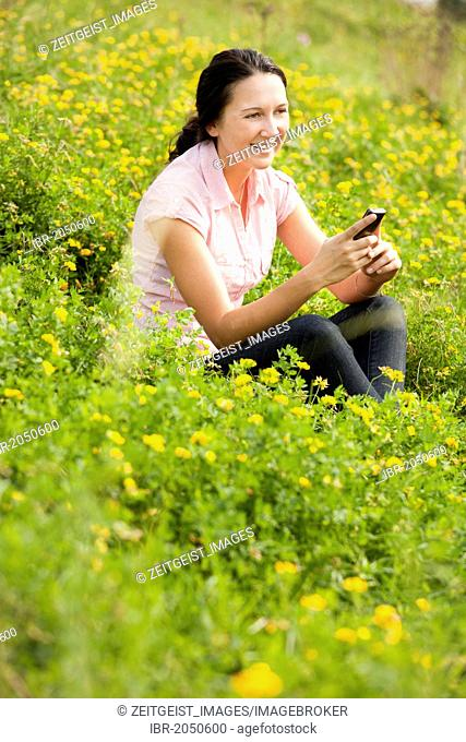 Smiling young woman sitting on a meadow, using a mobile phone