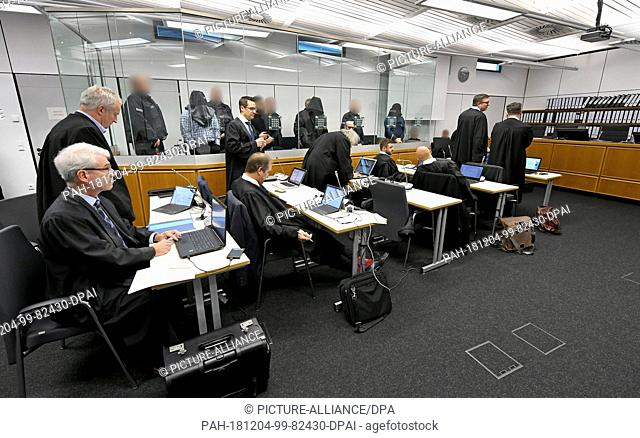 04 December 2018, Lower Saxony, Celle: The defendants and their defenders will stand in a courtroom of the Higher Regional Court before the start of the trial