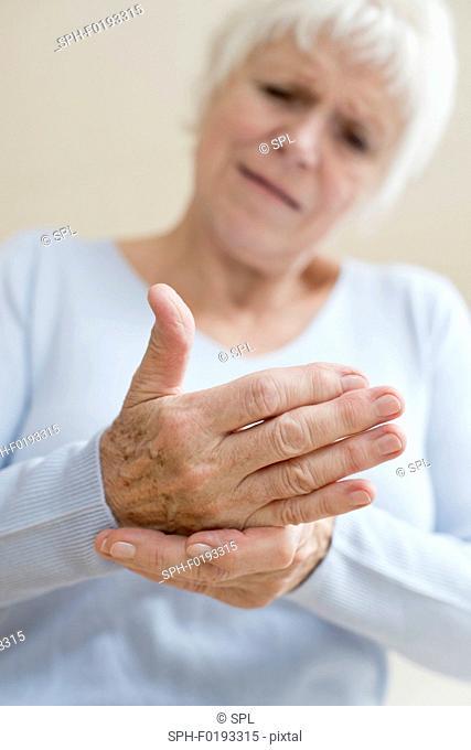 Senior woman touching sore hand