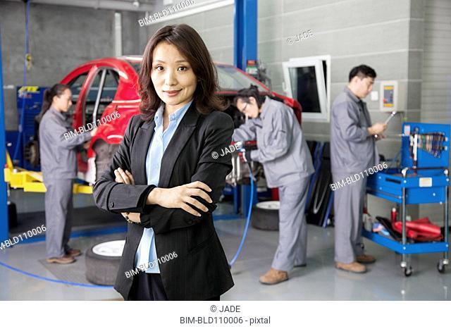Chinese businesswoman in mechanic garage