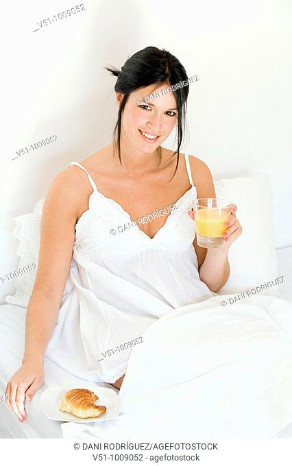 Brunette woman enjoying breakfast in bed