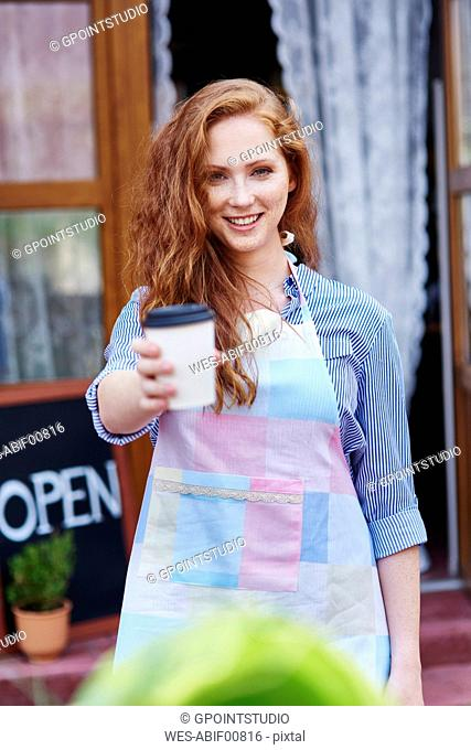 Portrait of smiling waitress offering a coffee