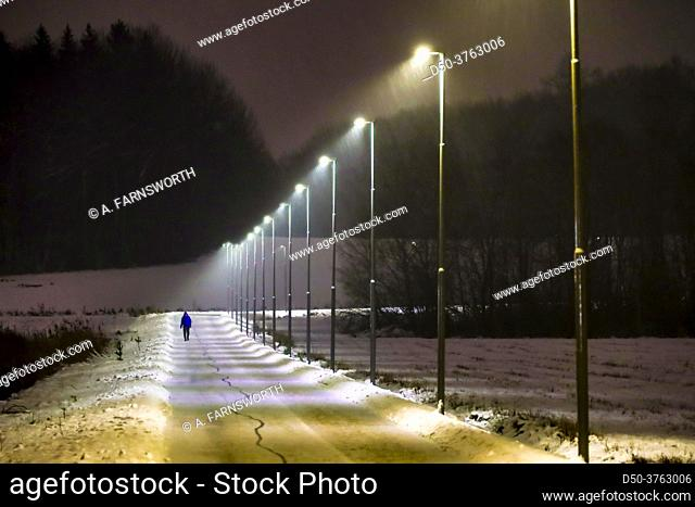 Stockholm, Sweden A man walks on a snowy illuminated path in the suburb of Huddinge