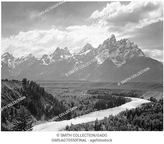 Black and white photograph, view from river valley towards snow covered mountains, river in foreground from left to right, captioned 'Grand Teton National Park'