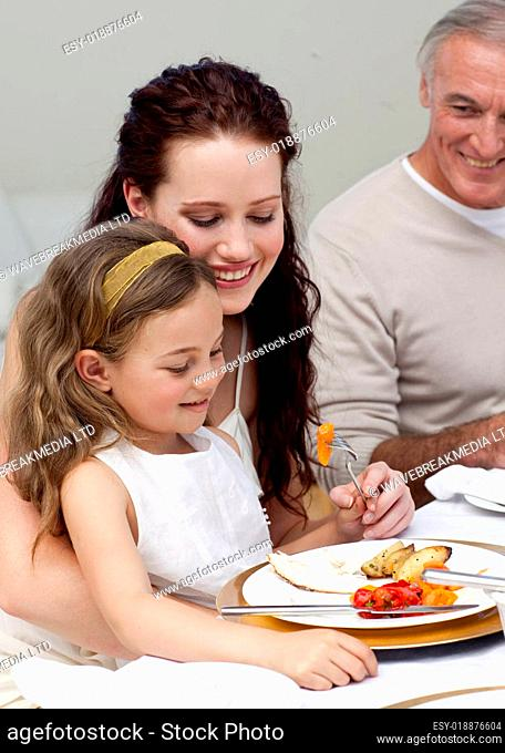 Mother and daughter eating with their family