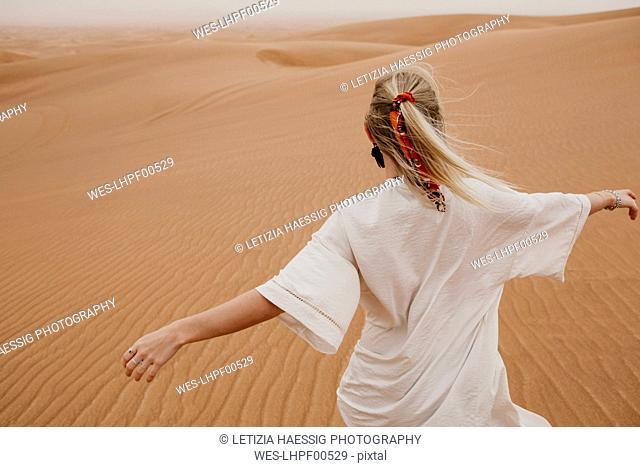 United Arab Emirates, Dubai, Lahbab Desert, woman walking in desert landscape