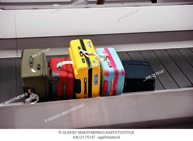 Colorful suitcases, luggage on airport baggage claim conveyor carousel, Narita International Airport, Japan