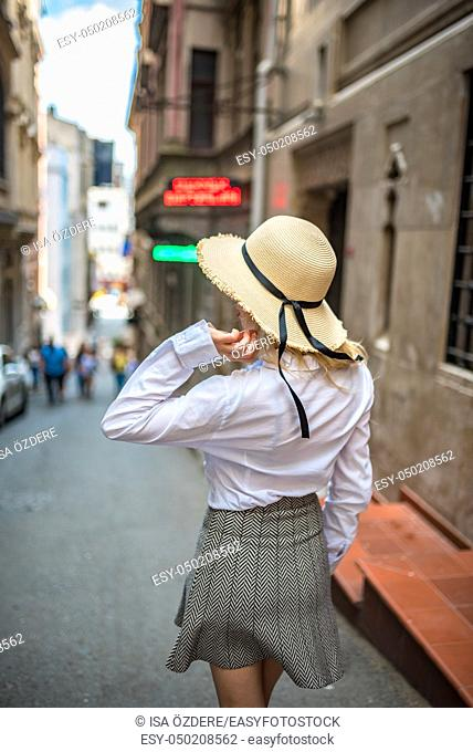 Back view of attractive fashionable girl with trendy clothes and hat walks at the street. Traveler concept