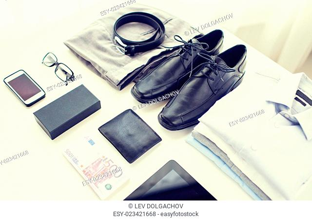 business, style, clothes and objects concept - close up of formal male clothes and personal stuff on table at home