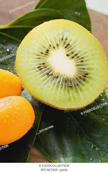 Half a kiwi fruit and two kumquats on leaves