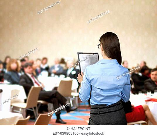 Beautiful business woman is speaking on conference