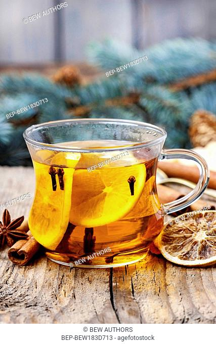 Glass of hot steaming tea among christmas decorations on wooden table