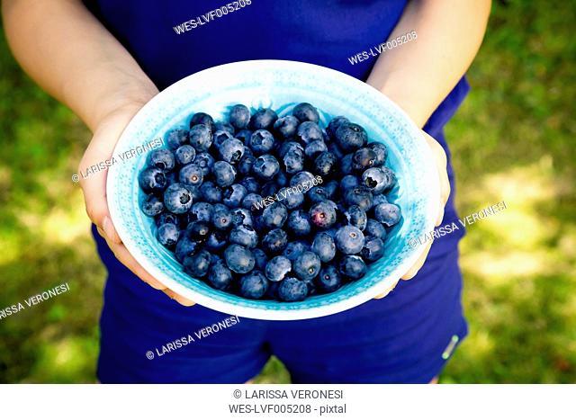 Girl's hands holding bowl of blueberries