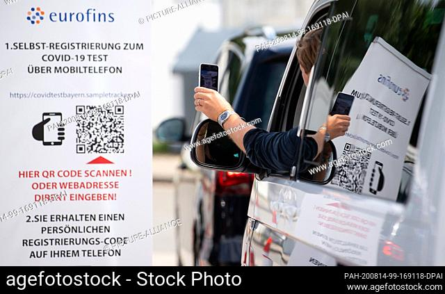 14 August 2020, Bavaria, Kiefersfelden: A man scans a QR code with his smartphone at a corona test centre on the A93 motorway at the Inntal-Ost rest stop